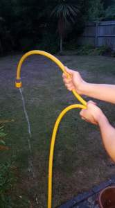 Demonstrating a compressed nerve by showing restricted water flow through a hosepipe to accompany the blog by Lizzie Wright on sciatica