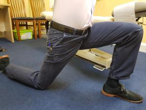 Anterior hip stretch demonstrated as described, performed on a mat on the floor