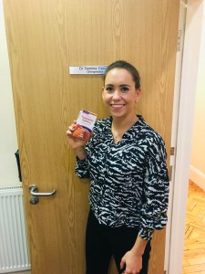 Image shows Eastbourne Chiropractor Gemma Crouch at Lushington Chiropractic holding a carton of Lamberts Turmeric Food Supplements to accompany her blog on the Benefits of turmeric