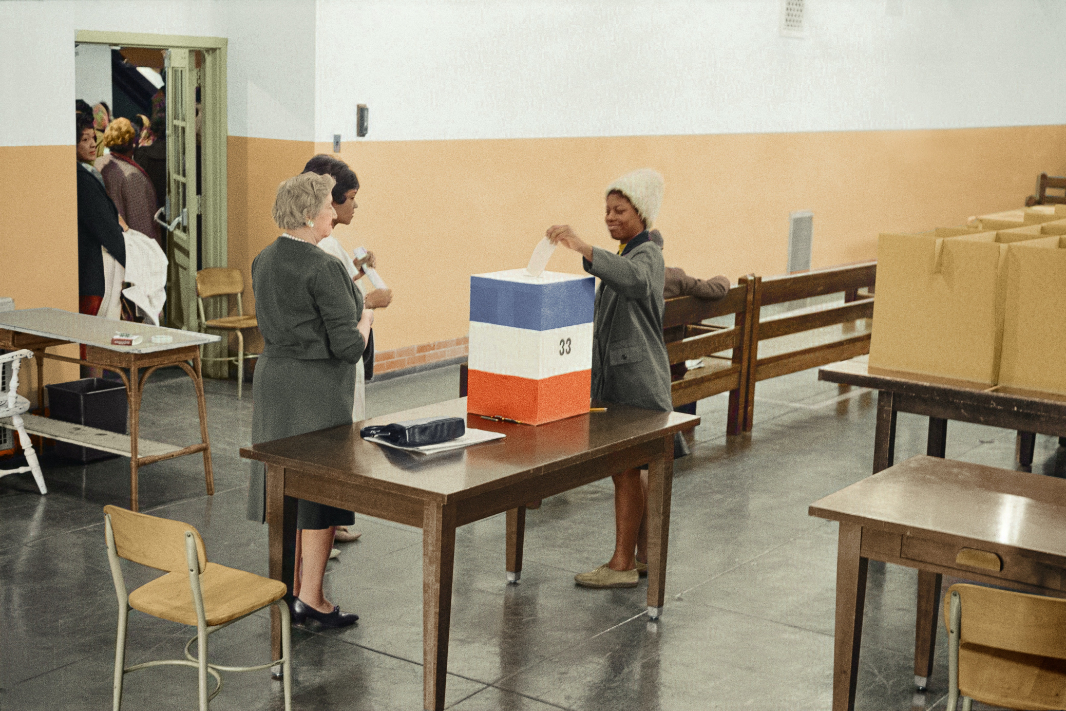 A Black woman in the 1960s places a ballot in a ballot box as two white women watch.