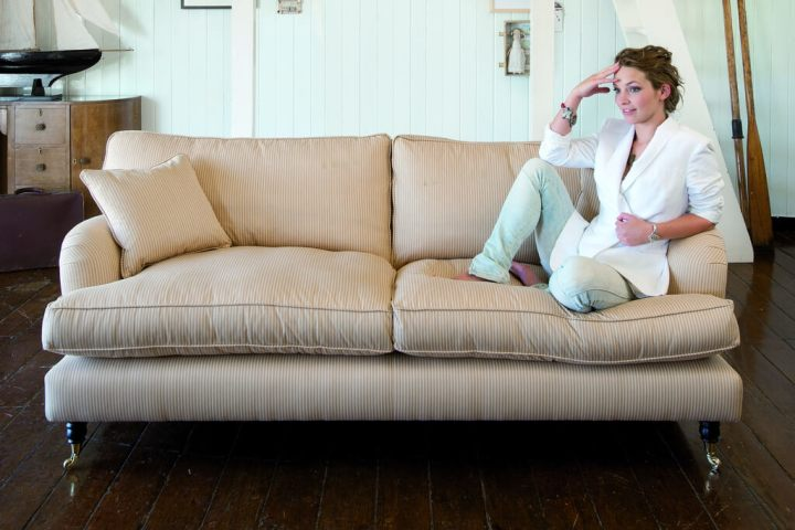 woman relaxing on cream sofa-best sofa for back support