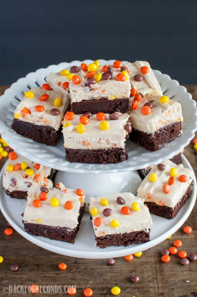 Reese's Pieces Peanut Butter Cheesecake Brownies on a double decker cake stand