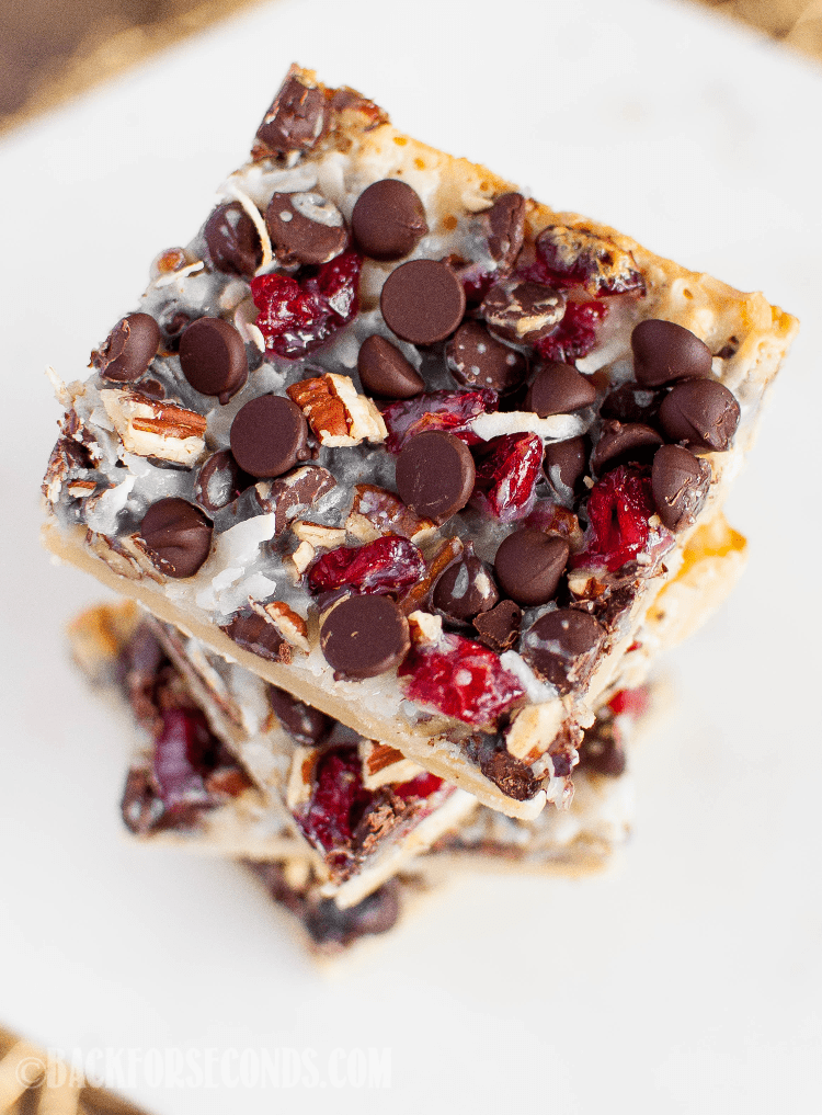 Dark Chocolate Cranberry Magic Bars are a symphony of flavors and textures, perfect for the holiday baking season! Easy to make and beyond delicious! #christmasdessert #thanksgivingdessert #holidaybaking #cranberrydessert