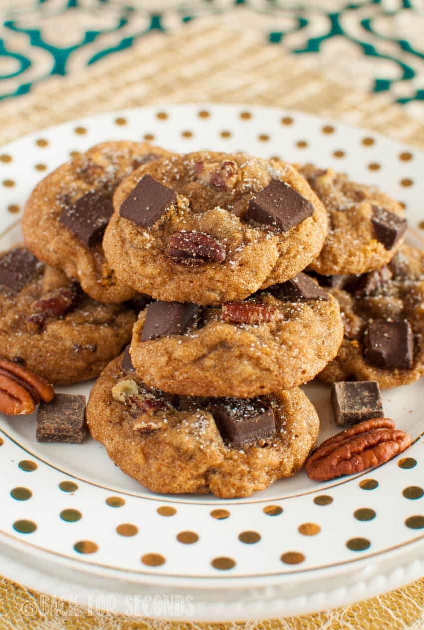 Molasses Chocolate Chunk Cookies piled on a white and gold poles dot plate