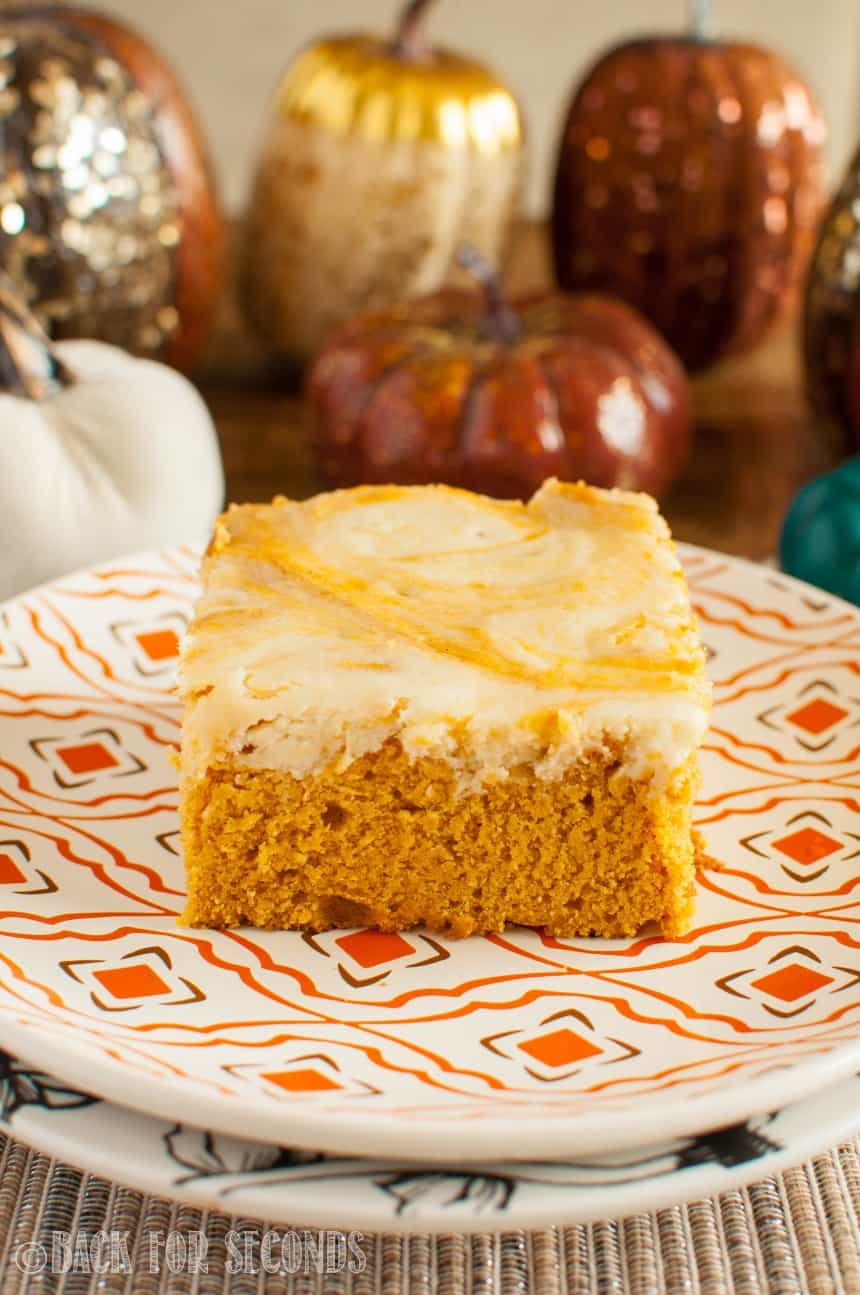 Pumpkin Cheesecake Swirl Bars on a plate with pumpkins in the background
