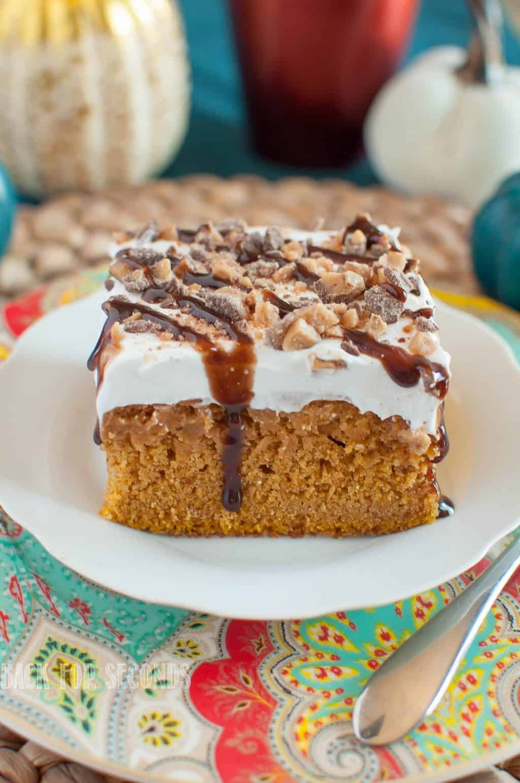 Pumpkin Butterscotch Poke Cake drizzled with chocolate and toffee on a white plate