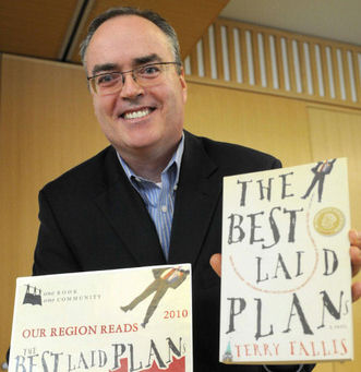 """Image: Terry Fallis with his book, """"The Best Laid Plans"""""""