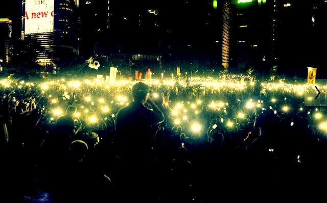 Protestors hold lights aloft