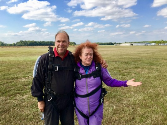 two skydivers on field after jump