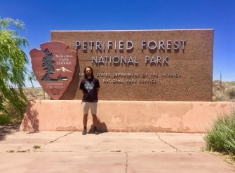 Man standing with Petrified Forest National Park sign