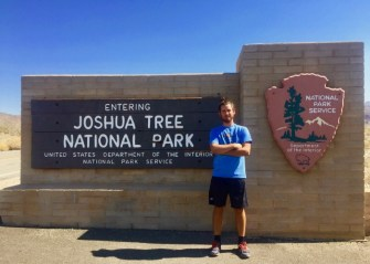 Man standing with Joshua Tree National Park sign