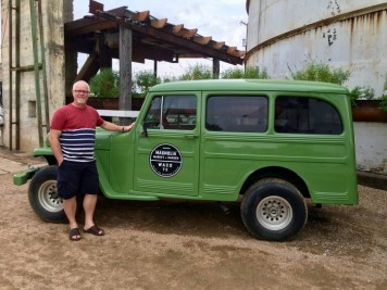 man standing by vintage SUV Magnolia Market