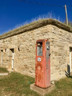 vintage gas pump and stone building with sod roof