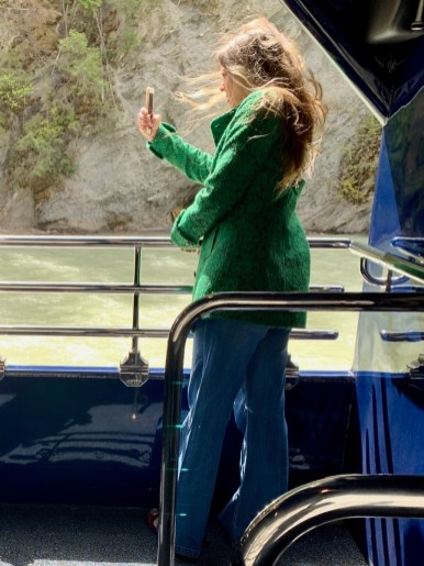 Woman taking pictures from the Rocky Mountaineer Train Vestibule