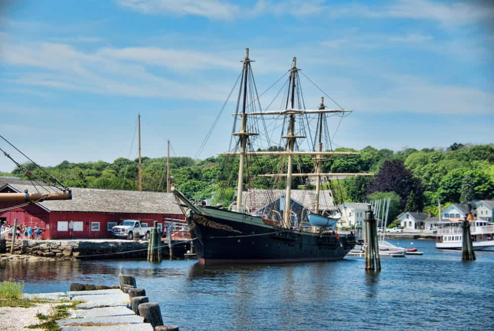 A tall ship anchored in the harbor at Mystic Seaport