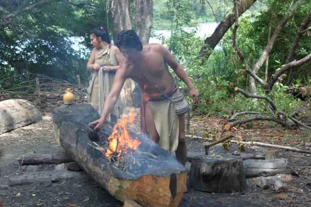 Two Wampanoag tribes people showing visitors how to make a traditional dugout canoe.