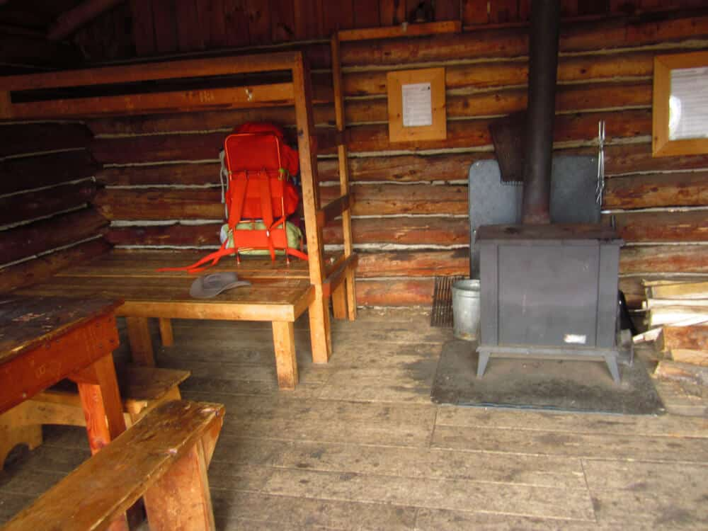 An inside view of Ridge Cabin - woodstove, wooden bunks, and a bright orange backpack