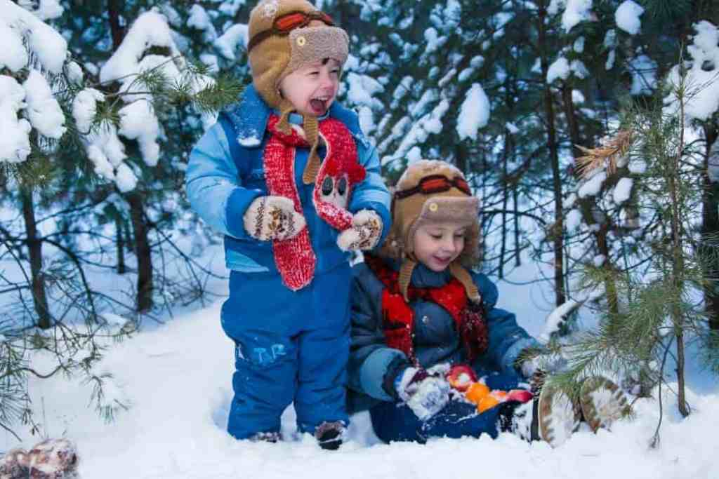 Two boys in winter clothing stand in a snowy forest. One of the boys is holding some oranges.