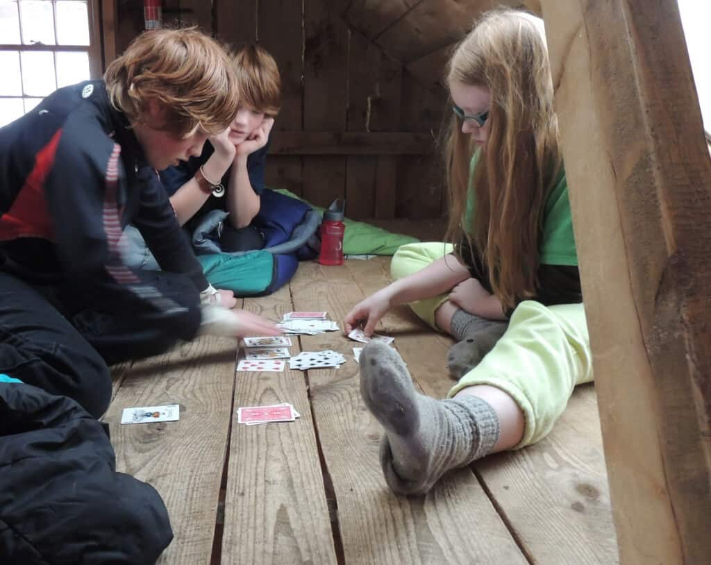 three kids playing cards on a wood floor