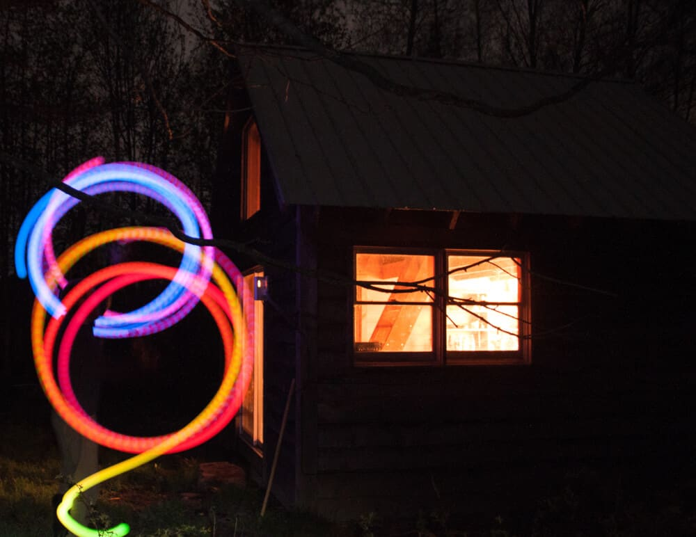 A night shot of an lighted window and colorful circles created by spinning poi.