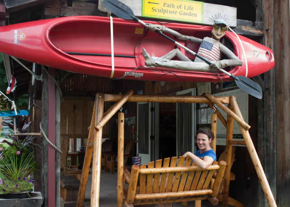 The entrance of Great River Outfitters, including a kayak paddled by a driftwood sculpture and a wooden bench swing.
