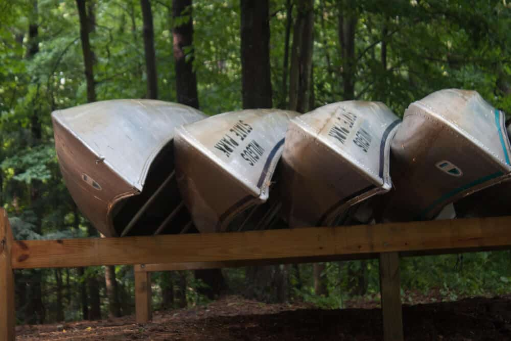 4 canoes up on a wooden rack at Wilgus State Park in Vermont