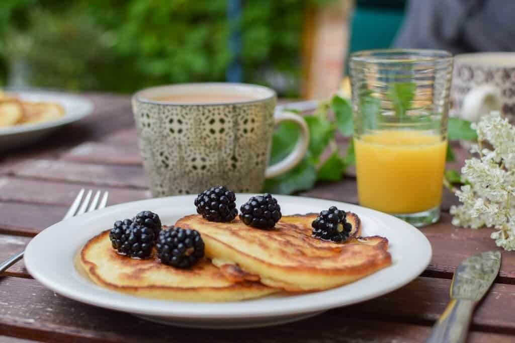 pancakes topped with blackberries on a picnic table next to a cup of coffee and a glass of orange juice.