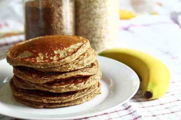 A stack of pancakes sit on a plate next to a banana.