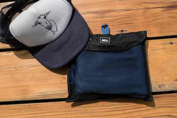 An REI multi towel next to a baseball cap