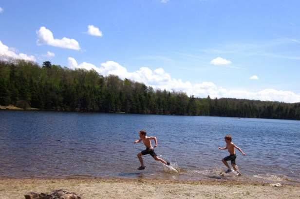 An image of two children running through the water at Woodford State Park. Best hikes for kids in Southern Vermont.