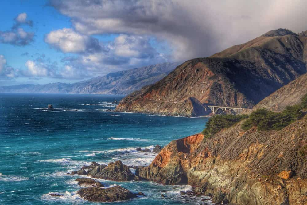 The rocky coastline of Big Sur with turquoise waters and cloudy skies
