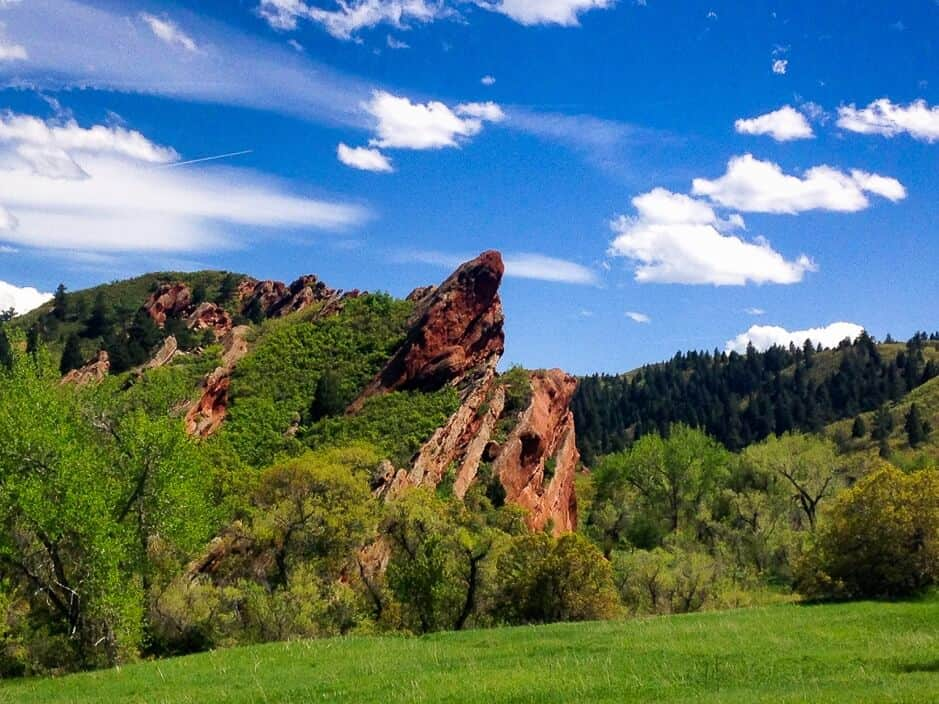 A nature scene - Red rocks jutting toward a blue sky, with green trees and grass all around.