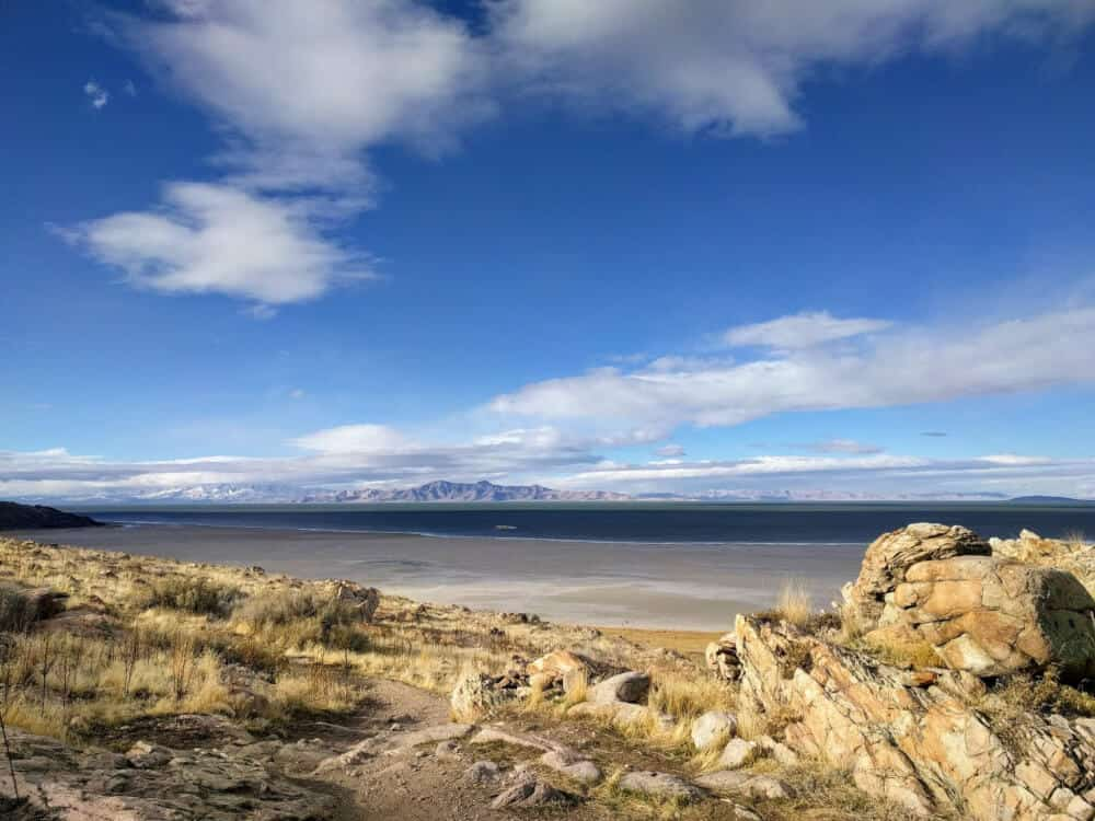 A scene of Antelope Island State Park in Utah - yellow rocks leading to the Great Salt Lake, with distant mountains and a clear blue sky.