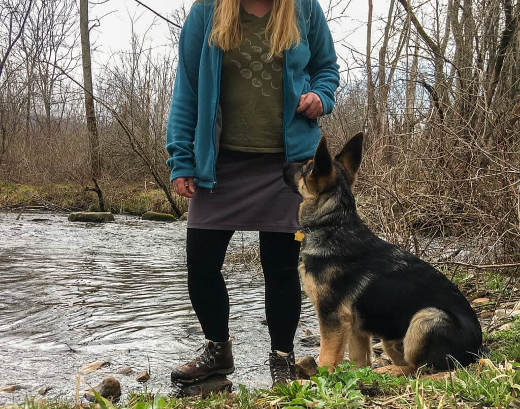 Me, standing in front of a river with Neil, the German Shepherd pppy