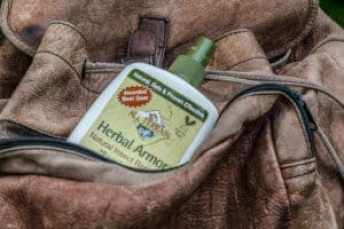 a leather backpack with a bottle of herbal armor bug spray
