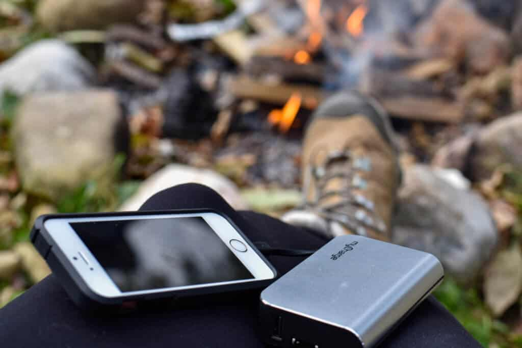 A cell phone connected to a portable charger, near a campfire