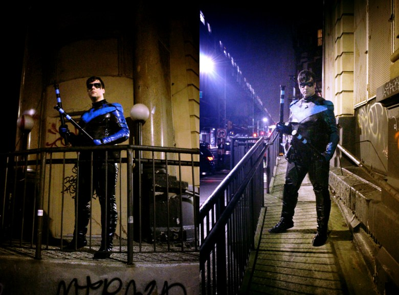 Nightwing in front of a Gotham City background.