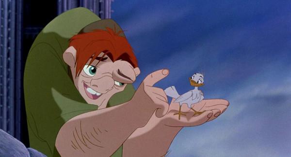 Quasimodo holds bird in hand.