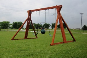 A stand-alone Backyard Fun Factory redwood swing set with two belt swings and a punching back is pictured on a large expanse of grass with trees and horses in the background.
