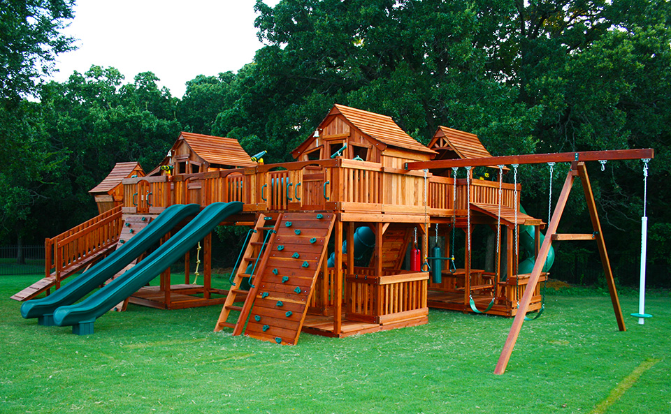 A picture of a couple of Backyard Fun Factory Fort Stockton Redwood Playsets bridged to a Mustang Redwood Playset