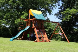 Children swing and play on a Rustler style redwood swing set from Backyard Fun Factory's Cowtown Series. The set features a 5 foot deck height, swings a slide, a tarp roof, and more.