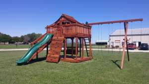 Redwood playset at Justin playground factory. Kids outdoor playset with a slide and swings.