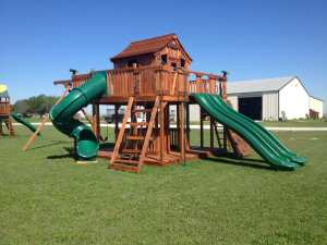 Custom backyard playset with slides, swings, spiral slide and cabin at Justin playground store.