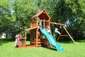 Several kids play on a Wrangler style redwood swing set from Backyard Fun Factory's Cowtown Series. It features a 5 foot deck height, slide, swings, and a lemonade stand.