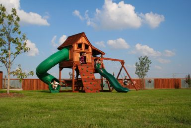 Maverick 6' playset with Upper Cabin, twister slide, cabin, rock wall, swing set, swings, and slide. Children playing on playground with playset accessories in the backyard.
