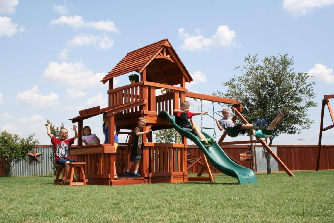 This 6 foot Fort Davis redwood playset features a slide, a swing set, and a lemonade stand, proving that redwood playsets are perfect for engaging kids of all ages.