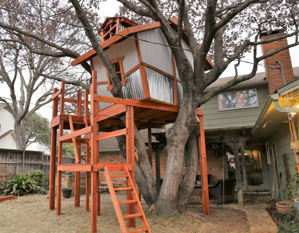 back side of whimsical treehouse, deck ladders accessing decks, dormer shown with crooked windows, kids tree house