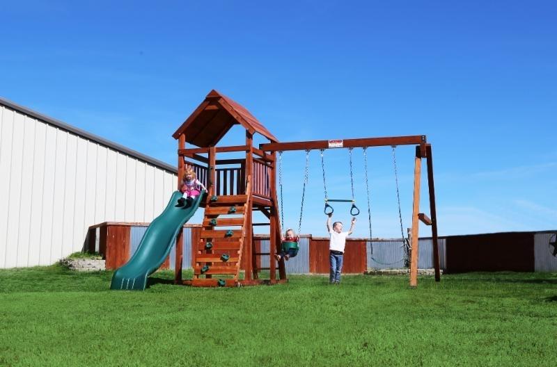 belt swings, ladder, playset, rock wall, slide, swing set, trapeze bar, wood roof, wrangler, outdoor playset, children