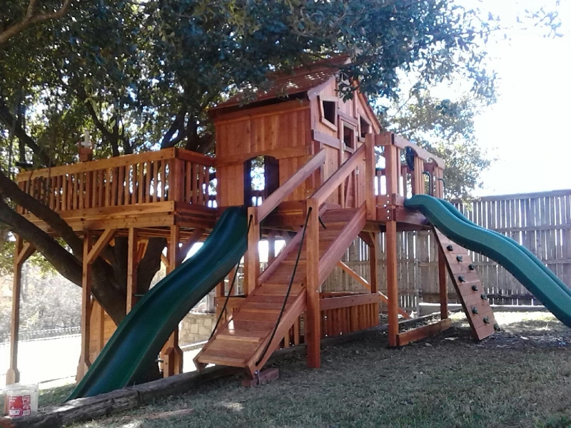 belt swings, cabin, fort stockton, fun deck, overhead climber, ramp, rock walls, ships wheel, slide, swing beam, trapeze bar, tree deck, wooden playset