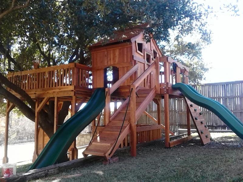 belt swings, cabin, fort stockton, fun deck, overhead climber, ramp, rock walls, ships wheel, slide, swing beam, trapeze bar, tree deck, wooden playset